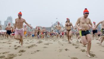 2017-01-01 12:01:08 SCHEVENINGEN - Deelnemers aan de traditionele Unox Nieuwjaarsduik rennen massaal de Noordzee in. ANP BART MAAT