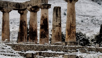 2017-01-08 11:43:33 A person walks by the snow-covered temple of Apollon in Ancient Corinth on January 8, 2017. Greece experiences rare cold wave with low temperatures and snowfalls in many regions of the country.  / AFP PHOTO / VALERIE GACHE