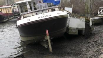 2017-01-01 14:36:19 GENNEP - Woonboten hangen onveranderd scheef nadat het waterpeil in de Maas is gezakt als gevolg van het ongeval bij de stuw van de John S. Thompson brug bij Grave. ANP MARCEL VAN HOORN